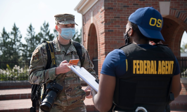 U.S. Air Force photojournalist speaks with officer