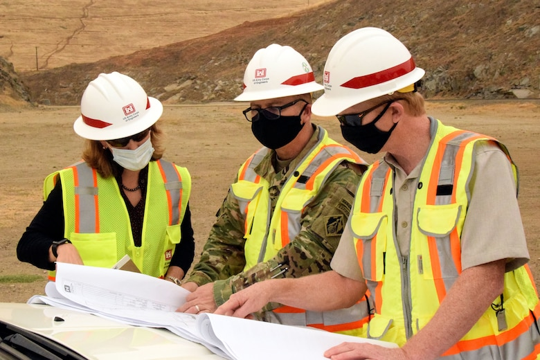 USACE Sacramento District Commander COL James Handura (center) and other project leaders go over construction plans as groundbreaking gets underway on the Tule River Spillway Enlargement Project at Success Lake near Porterville, California.