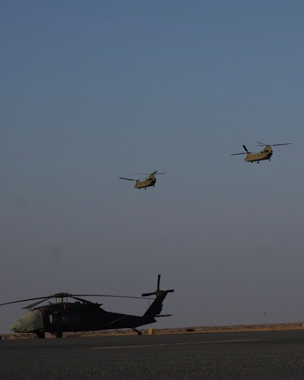 CH-47 Chinook helicopters, operated by Soldiers with Bravo Company, 2-104th General Support Aviation Battalion, 28th Expeditionary Combat Aviation Brigade take off from an airfield for a local area orientation flight in the 28th ECAB's area of operations after arriving in the Middle East. These flights ensure 28th ECAB aircrews are properly acclimated and can conduct missions safely during the deployment. (U.S. Army photo by Spc. Jose Brown)