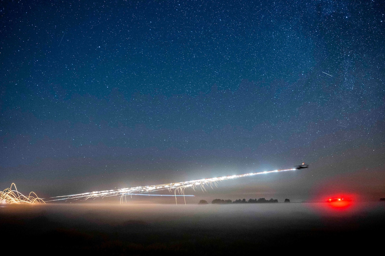 A helicopter fires rockets at night.