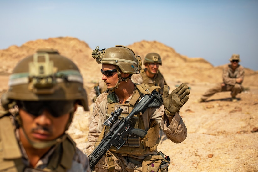 Four Marines stand behind each other in a desert terrain.