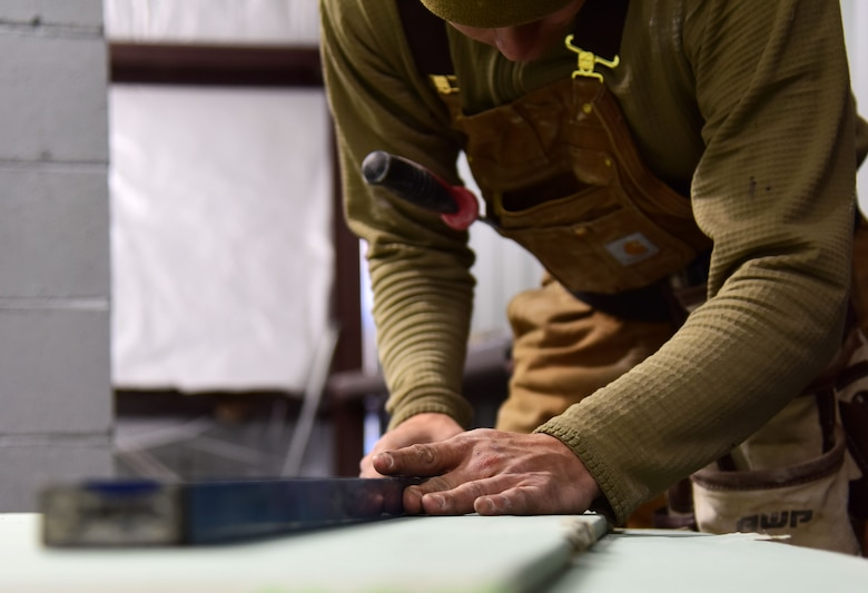 U.S. Air Force Staff Sgt. James Ori, a 554th Rapid Engineer Deployable Heavy Operational Repair Squadron Engineers (RED HORSE) structural craftsman, cuts off a piece of drywall at Eielson Air Force Base, Alaska, Sept. 10, 2020.