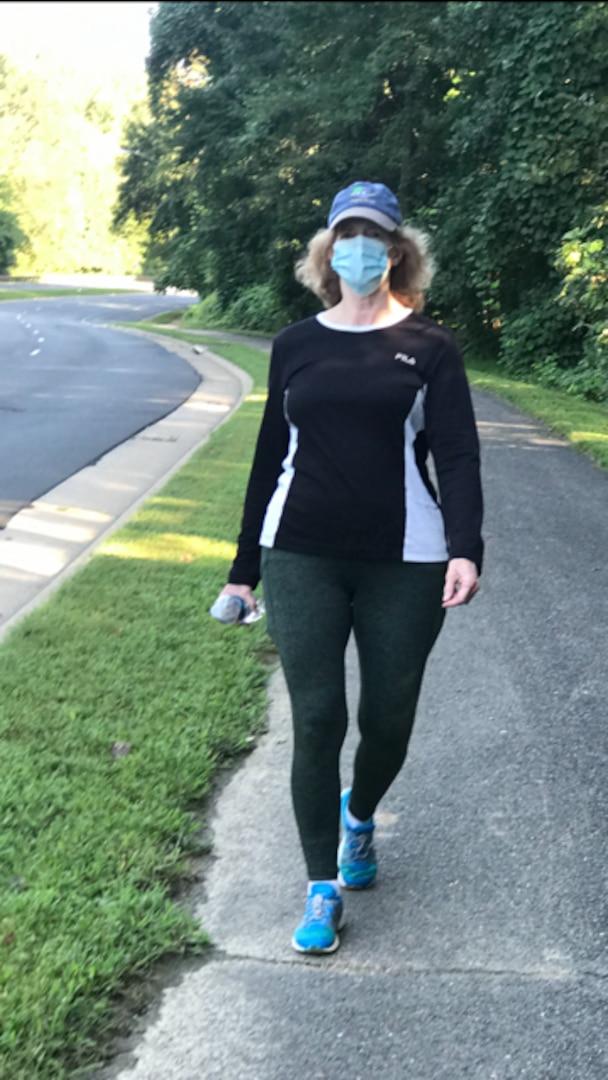 Woman wearing cap and mask walks along a sidewalk.