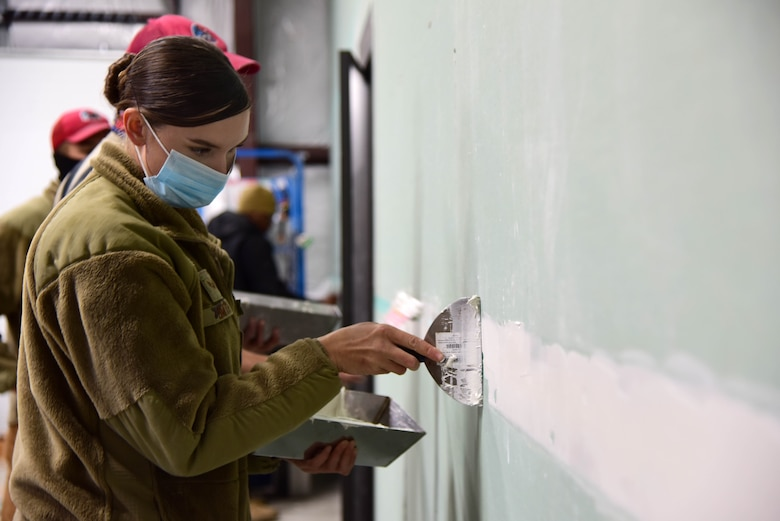 U.S. Air Force Senior Airman Savannah Smith, a 554th Rapid Engineer Deployable Heavy Operational Repair Squadron Engineers (RED HORSE) structures journeyman, applies joint compound to a building partition at Eielson Air Force Base, Alaska, Sept. 10, 2020.