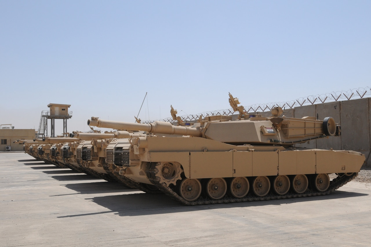Military tanks sit side-by-side in a secure outdoor compound.
