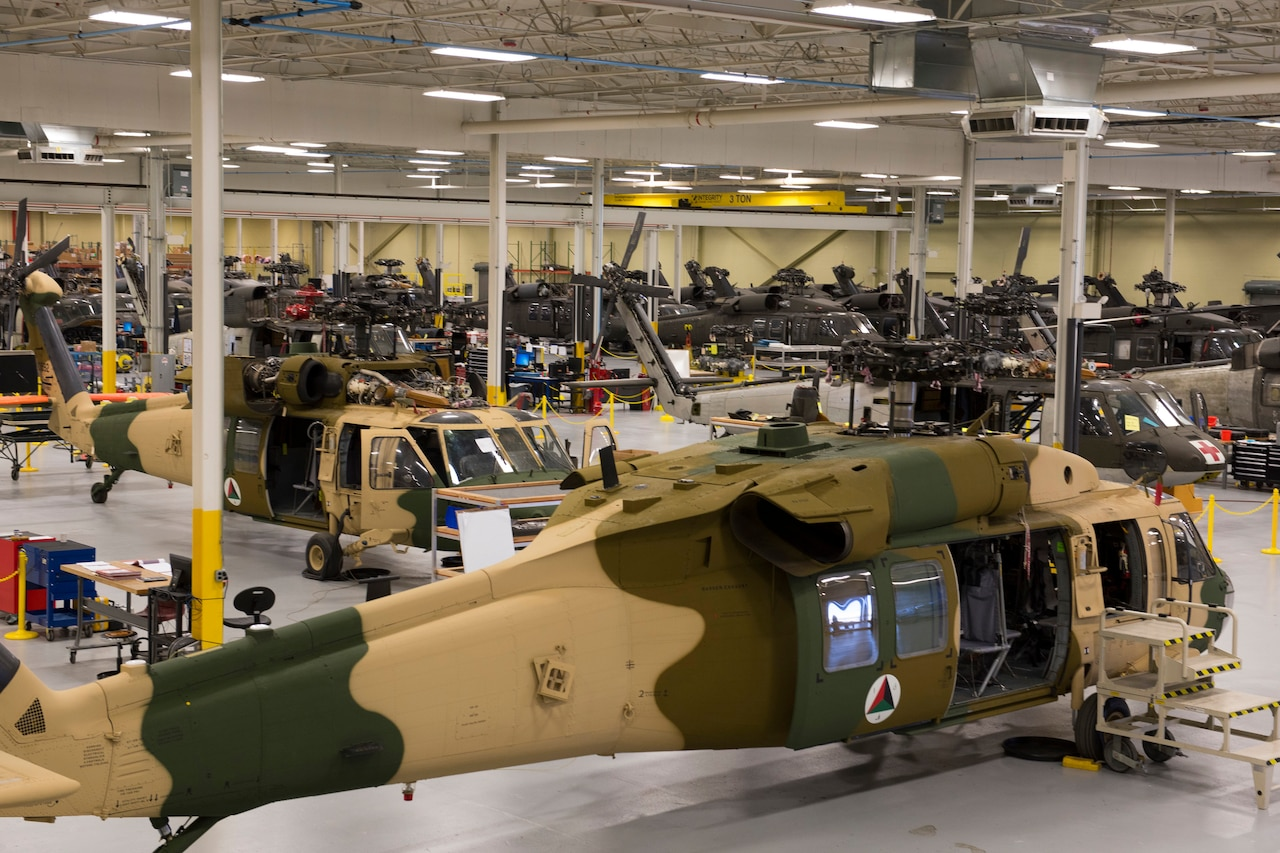 A large warehouse facility contains more than a dozen military helicopters.