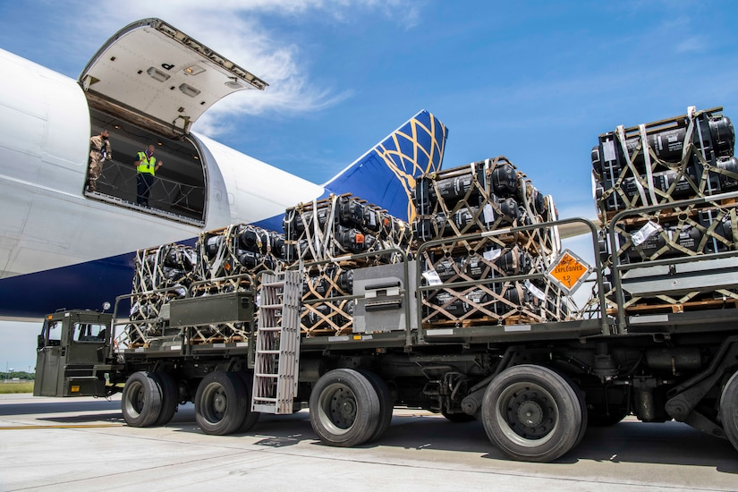 A large loader truck with cargo is backed up to an aircraft.