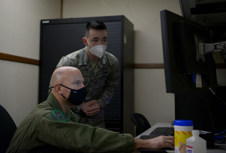 U.S. Air Force Airman 1st Class Jared Clark, a 354th Communications Squadron (CS) client systems technician, teaches Col. David Berkland, the 354th Fighter Wing (FW) commander, how to mitigate network vulnerabilities on Eielson Air Force Base, Alaska, Sept. 29, 2020. The 354th CS manages, operates, maintains and provides communications to support the 354th FW's combat and support missions. (U.S. Air Force photo by Senior Airman Beaux Hebert)