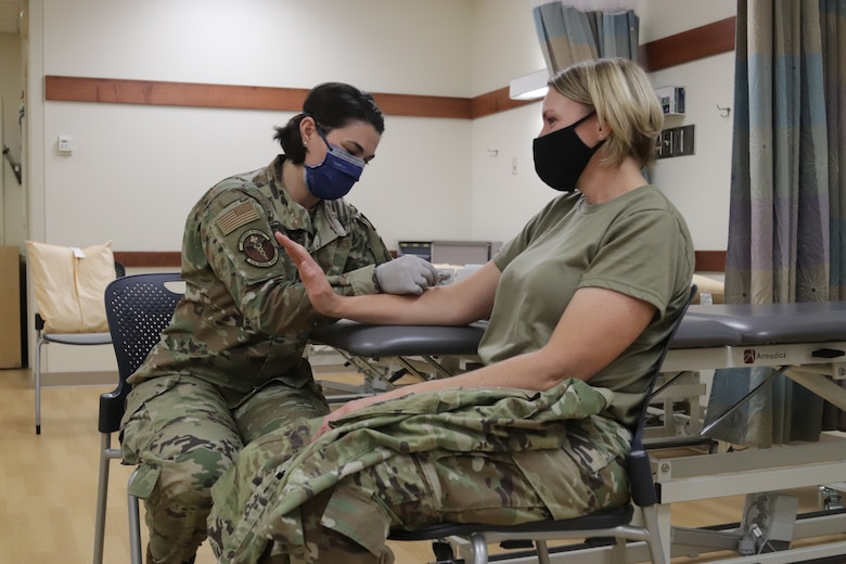 U.S. Air Force Capt. Jaime Briske, 673d Medical Operations Squadron staff physical therapist, inserts a dry needle into the arm of U.S. Air Force Col. Kirsten Aguilar, Joint Base Elmendorf-Richardson and 673d Air Base Wing commander, during a 673d MDOS immersion tour at JBER, Alaska, Sept. 24, 2020. Aguilar familiarized herself with the 673d MDOS and its role in supporting installation readiness after taking command of the installation on July 14, 2020. The 673d MDOS works to enhance the performance and overall health of JBER in order to ensure combat effectiveness. (U.S. Air Force photo by Capt. Orlando Cabigas)