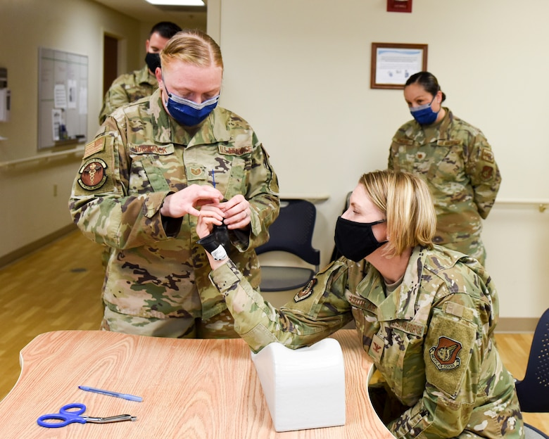 U.S. Air Force Tech. Sgt. Jacklyn Hammock, noncommissioned officer in charge of occupational therapy, demonstrates how a splint is made to U.S. Air Force Col. Kirsten Aguilar, Joint Base Elmendorf-Richardson and 673d Air Base Wing commander, during a 673d Medical Operations Squadron immersion tour at JBER, Alaska, Sept. 24, 2020. Aguilar familiarized herself with the 673d MDOS and its role in supporting installation readiness after taking command of the installation on July 14, 2020. The 673d MDOS works to enhance the performance and overall health of JBER in order to ensure combat effectiveness. (U.S. Air Force photo by Senior Airman Crystal A. Jenkins)