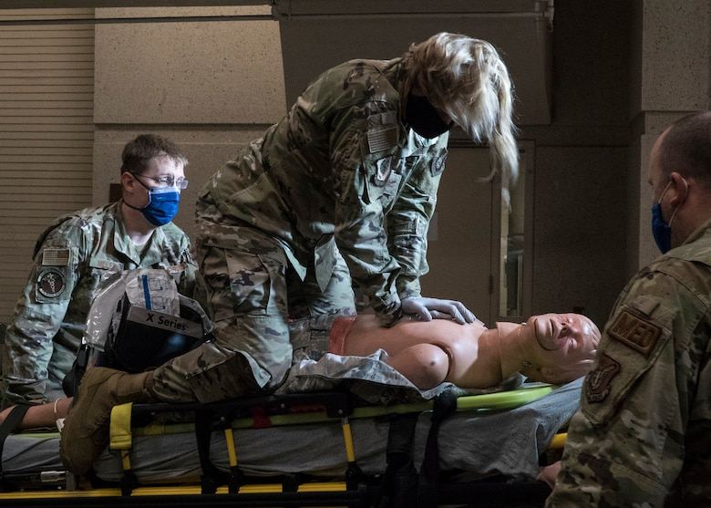 U.S. Air Force Col. Kirsten Aguilar, Joint Base Elmendorf-Richardson and 673d Air Base Wing commander, performs chest compressions during an exercise on a high fidelity manikin while U.S. Air Force Tech. Sgt. Benjamin Miller, paramedic, and U.S. Air Force Tech Sgt. Brock Ashbaugh, paramedic, assist in lifting the gurney from an ambulance during a 673d Medical Operations Squadron immersion tour at JBER, Alaska, Sept. 24, 2020. Aguilar familiarized herself with the 673d MDOS and its role in supporting installation readiness after taking command of the installation on July 14, 2020. The 673d MDOS works to enhance the performance and overall health of JBER in order to ensure combat effectiveness. (U.S. Air Force photo by Senior Airman Crystal A. Jenkins)
