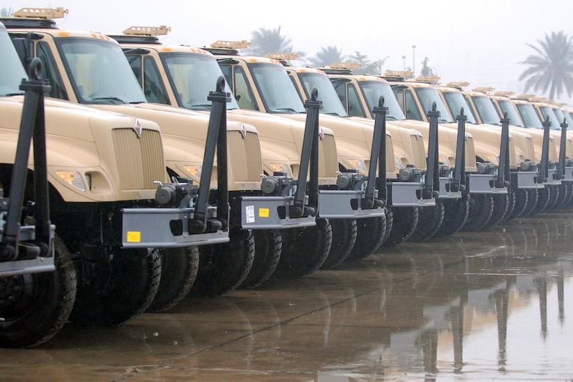 More than a dozen military vehicles sit side-by-side on a concrete slab.