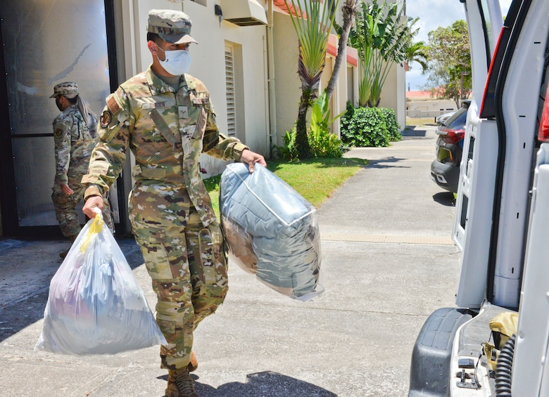 U.S. Air Force Airman 1st Class Timothy Garden, 36th Civil Engineering Squadron firefighter, carries bags of clothing and bedding to a van at Andersen Air Force Base, Guam, March 31, 2021. U.S. Air Force Airmen from squadrons across the 36th Wing gathered nearly 3,000 pounds of essential items provided by fellow service members, civilians, and dependents to donate to the Alee Shelter, a local nonprofit organization and safe house for women and children affected by domestic violence and sexual abuse. (U.S. Air Force photo by Alana Chargualaf)