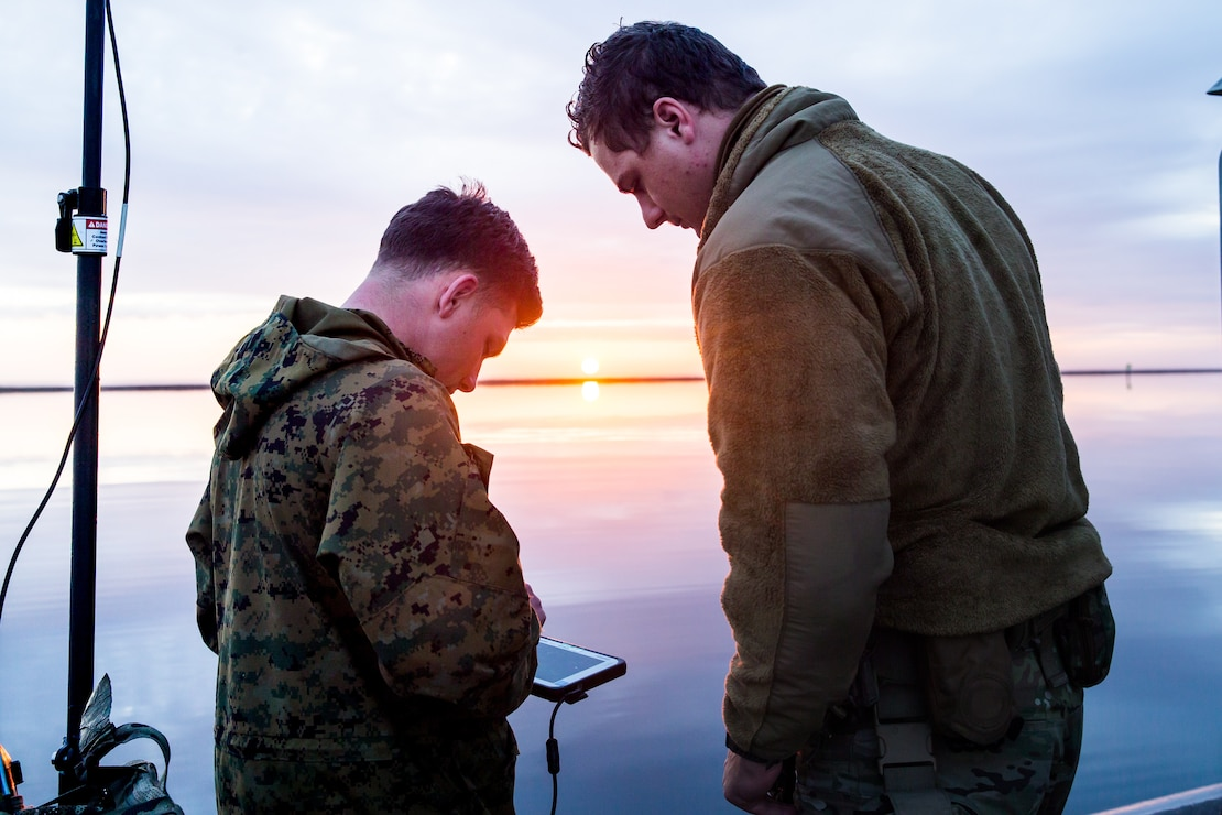 U.S. Marine Corps Sgt. Jeramiah Meade, Left, a section chief with 2nd Radio Battalion, 2d Marine Division, teaches U.S. Coast Guard Petty Officer 3rd Class Zachery Ribbons, Right, a North Benton, O.H., native and machinery crewman with Maritime Security Response Team East, how to use a electronic warfare system during a joint-service training exercise on Marine Corps Air Station Cherry Point, N.C., March 26, 2021. The purpose of the week-long training was to increase interoperability with the U.S. Coast Guard and provide 2d Marine Division reconnaissance battalions with the opportunity to become familiarized with quick reaction and counter electronic warfare concepts. (U.S. Marine Corps photo by Cpl. Elijah Abernathy)