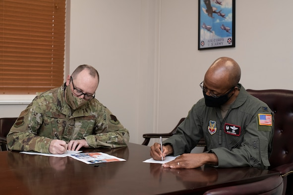 A photo of leadership filling out AFAF form for a story.