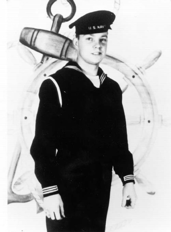 A young sailor in a Navy uniform and flat-top cap poses for a photo.