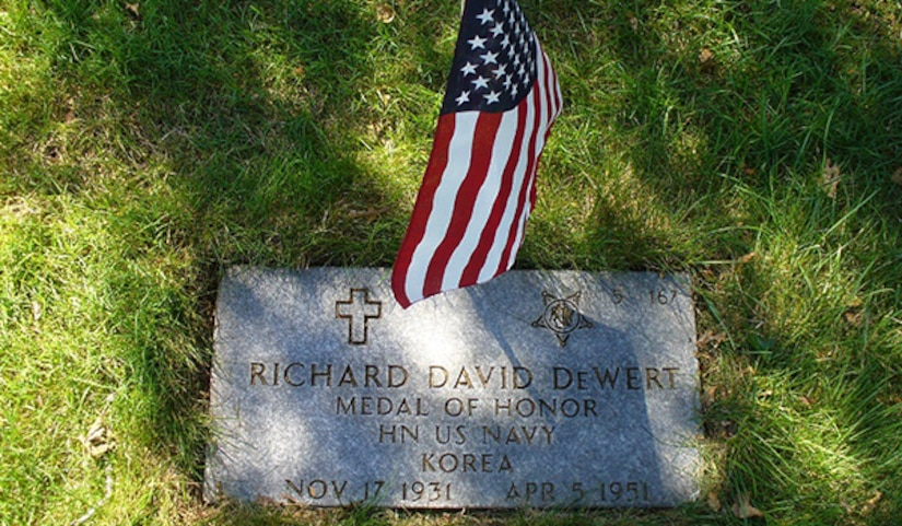 A grave marker on  the ground in a cemetery is decorated with a small American flag.