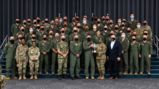 Leaders from U.S. Strategic Command, Strategic Command Consultation Committee and Airmen from the 96th Bomb Squadron pose for a photo with the Omaha Trophy at Barksdale Air Force Base, Louisiana, March 30, 2021. The Omaha Trophy is awarded each year to various units in recognition of outstanding support to USSTRATCOM's strategic deterrence mission. (U.S. Air Force photo by Airman 1st Class Jacob B. Wrightsman)
