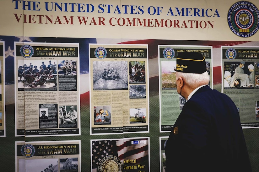 A man looks at a series of posters on a wall.