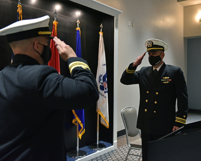 U.S. Navy Lt. Cmdr. John Allen, departing Navy Center for Information Warfare Training Detachment Goodfellow officer in charge, exchanges salutes with Lt. Cmdr. Mark Wess, Navy CIWT Detachment Goodfellow incoming commanding officer, during the Change of Charge ceremony at the Event Center on Goodfellow Air Force Base, Texas, March 31, 2021. This change of charge ceremony was a time to honor military tradition and signified the transfer of authority. (U.S. Air Force photo by Senior Airman Ashley Thrash)
