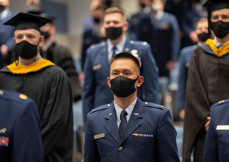 U.S. Air Force 2nd Lt. Benjamin Lam and his classmates take their seats at the start of the Air Force Institute of Technology graduation ceremony March 25, 2021, on Wright-Patterson Air Force Base, Ohio. Approximately 250 advanced degrees were awarded to Airmen, Space Force Guardians, Soldiers, Marines and Air Force civilians. (U.S. Air Force photo by R.J. Oriez)