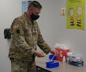 Staff Sgt. Benjamin Kilmer, site noncommissioned officer in charge for the Pennsylvania National Guard vaccination team at Capital Area Intermediate Unit in Enola, Pa., distributes vaccines to the different stations at the site on March 26, 2021.
