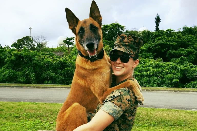 Marine Corps Sgt. Jenna Cauble poses for a photo with Bbutler, a military working dog.