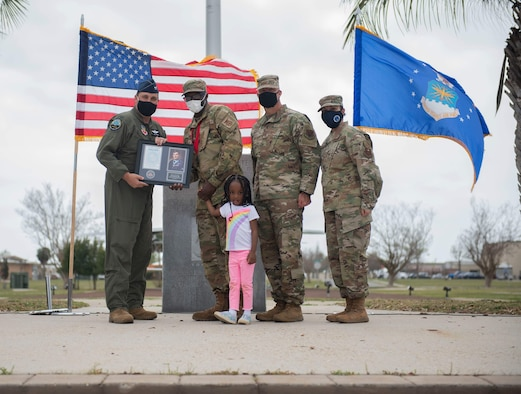An Airman accepts his award from leadership while holding his daughter's hand.