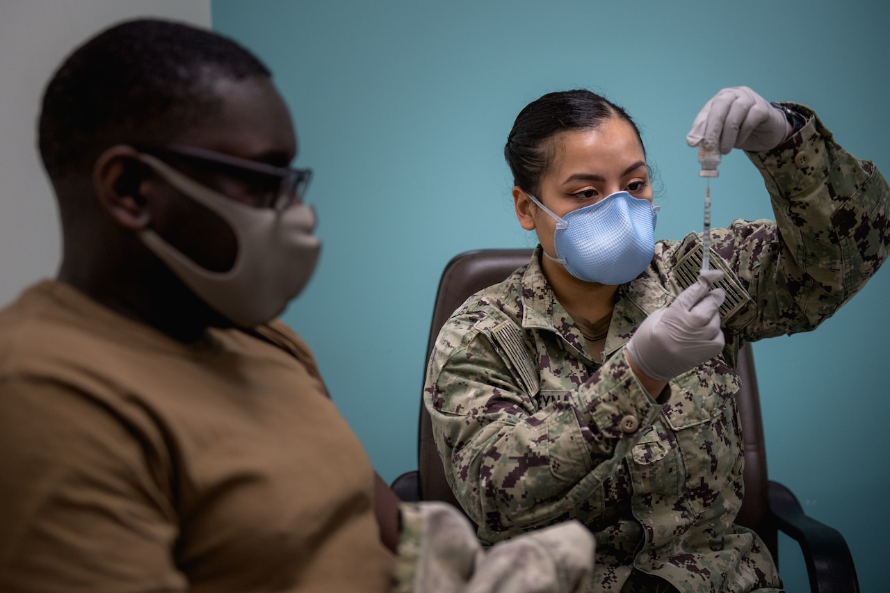 A sailor wearing gloves and a face mask prepares to vaccinate another sailor.