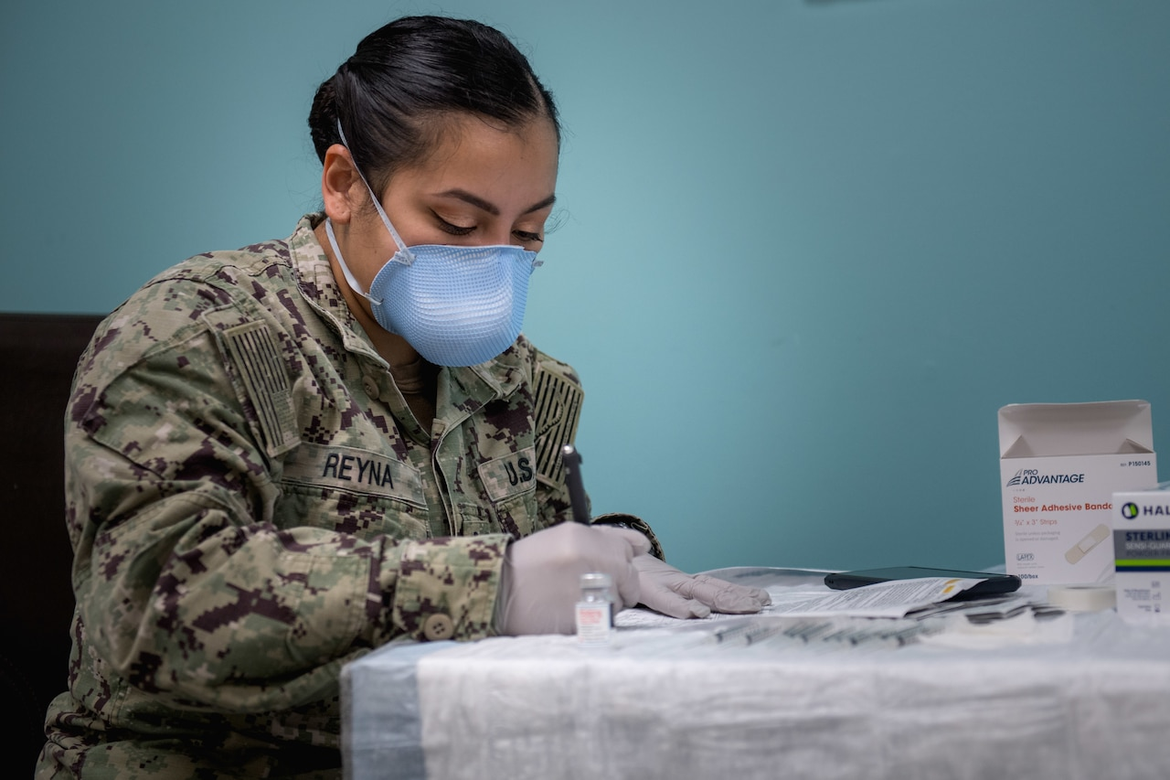 A sailor wearing a face mask and gloves fills out vaccine paperwork.