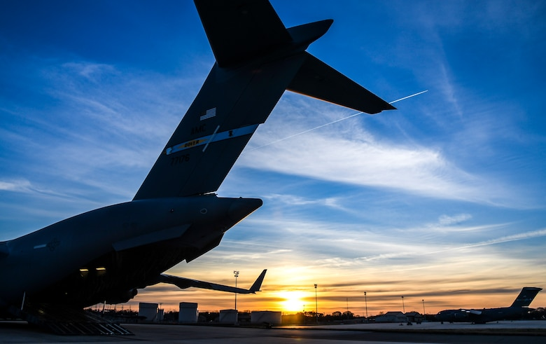 The sun sets over a C-17 Globemaster III aircraft on the flight line at Dover Air Force Base, Delaware, March 30, 2021. The 436th Airlift Wing owns, maintains and operates C-5M Super Galaxy and C-17 Globemaster III aircraft with a mission to provide rapid global airlift, combat ready Airmen and unrivaled installation support. (U.S. Air Force photo by Airman 1st Class Stephani Barge)
