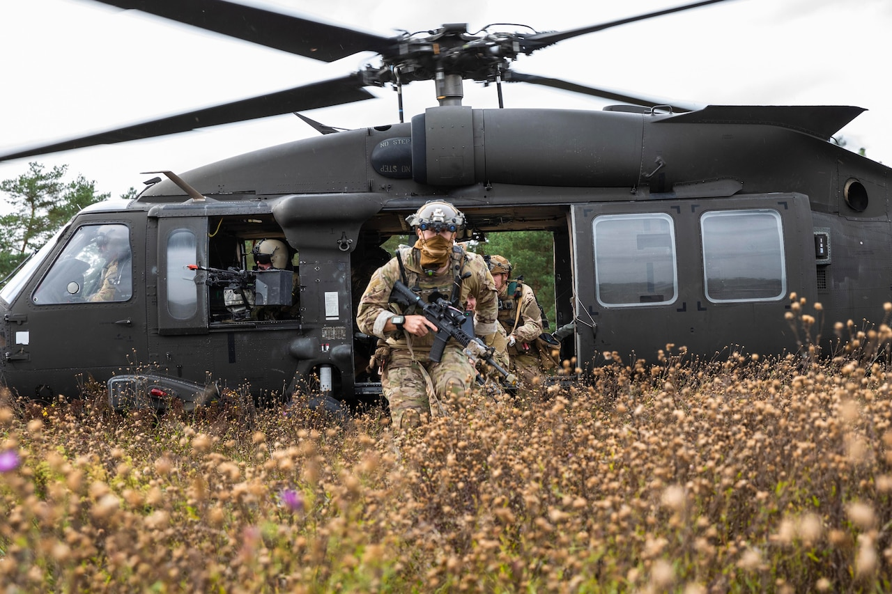 Troops exit helicopter in tall grass and weeds.