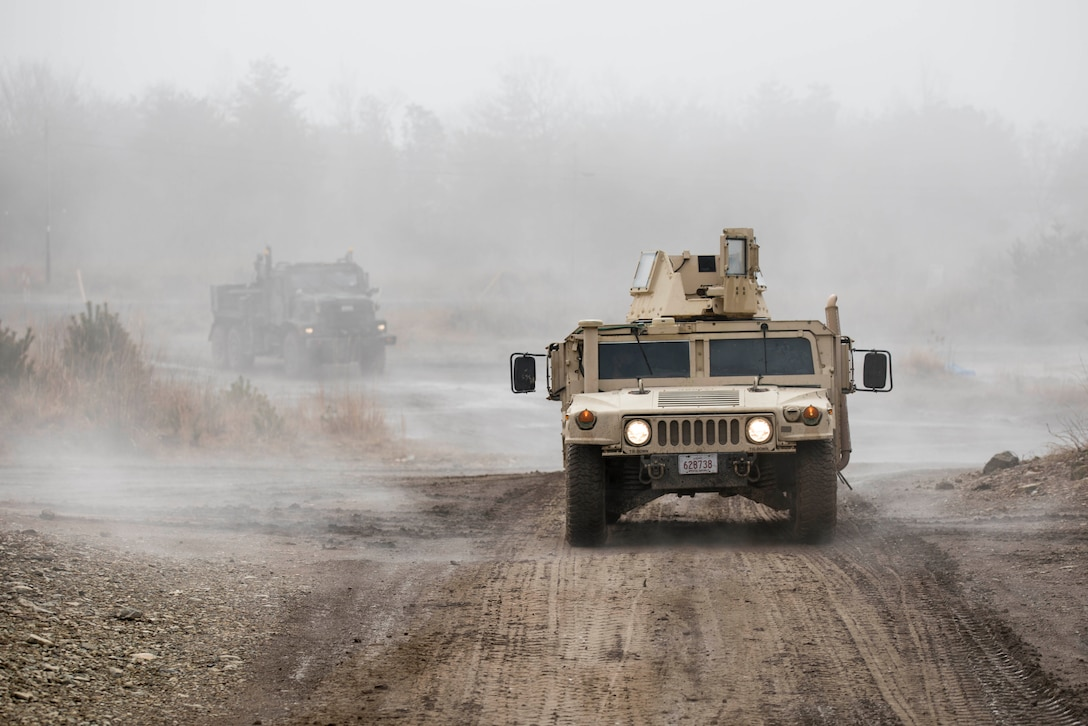 A Humvee and another vehicle drive along a dusty road.