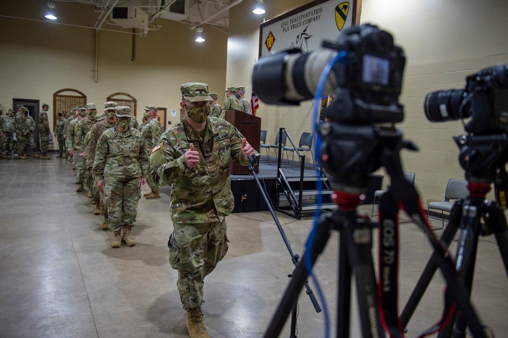 """A Soldier with the 345th Combat Sustainment Support Battalion gives a """"thumbs up"""" gesture to cameras broadcasting a virtual send-off ceremony at the National Guard armory in Ada, Oklahoma, April 1, 2021. The Soldiers are being mobilized to Fort Bliss, Texas in order to provide COVID mitigation support to units deploying overseas. (Oklahoma National Guard photo by Leanna Maschino)"""