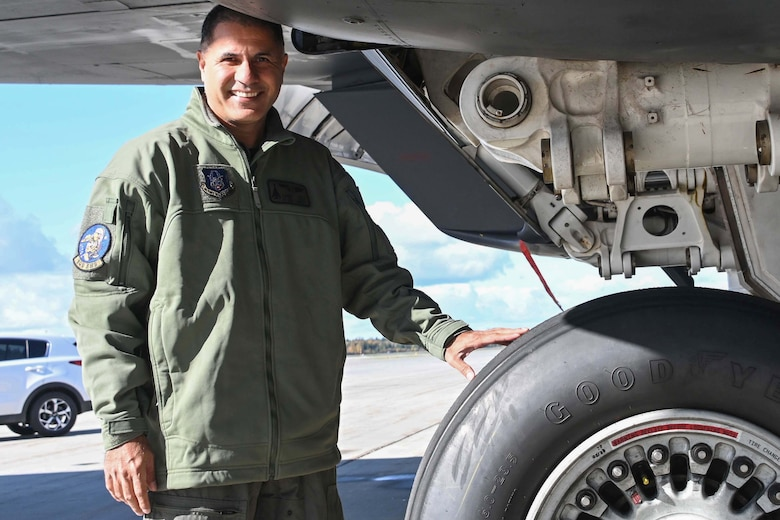 Photo of an Airman standing by the wheel of a B-1 Lancer bomber.