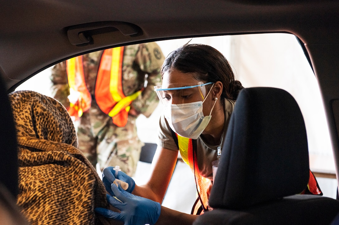 An airman wearing a face mask and gloves bends down to administer a COVID-19 vaccine to a resident sitting in a vehicle.