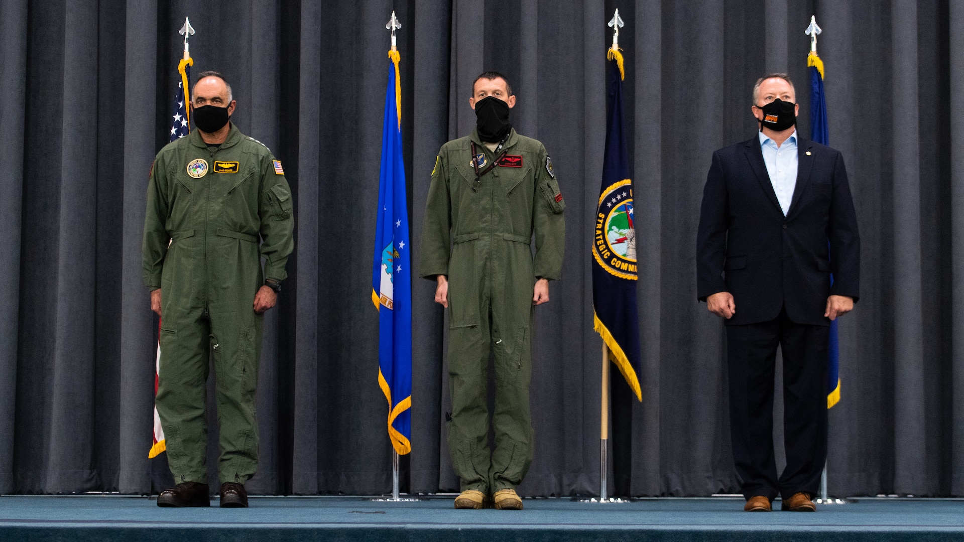 (Left to right) Adm. Charles Richard, U.S. Strategic Command commander, Lt. Col. Christopher Duff, 96th Bomb Squadron commander, and Mr. Tim Burke, Strategic Command Consultation Committee chairman, stand at the position of attention during the presentation of the Omaha Trophy to the 96th BS at Barksdale Air Force Base, Louisiana, March 30, 2021.The Omaha Trophy is awarded each year to various units in recognition of outstanding support to USSTRATCOM's strategic deterrence mission (U.S. Air Force photo by Airman 1st Class Jacob B. Wrightsman)