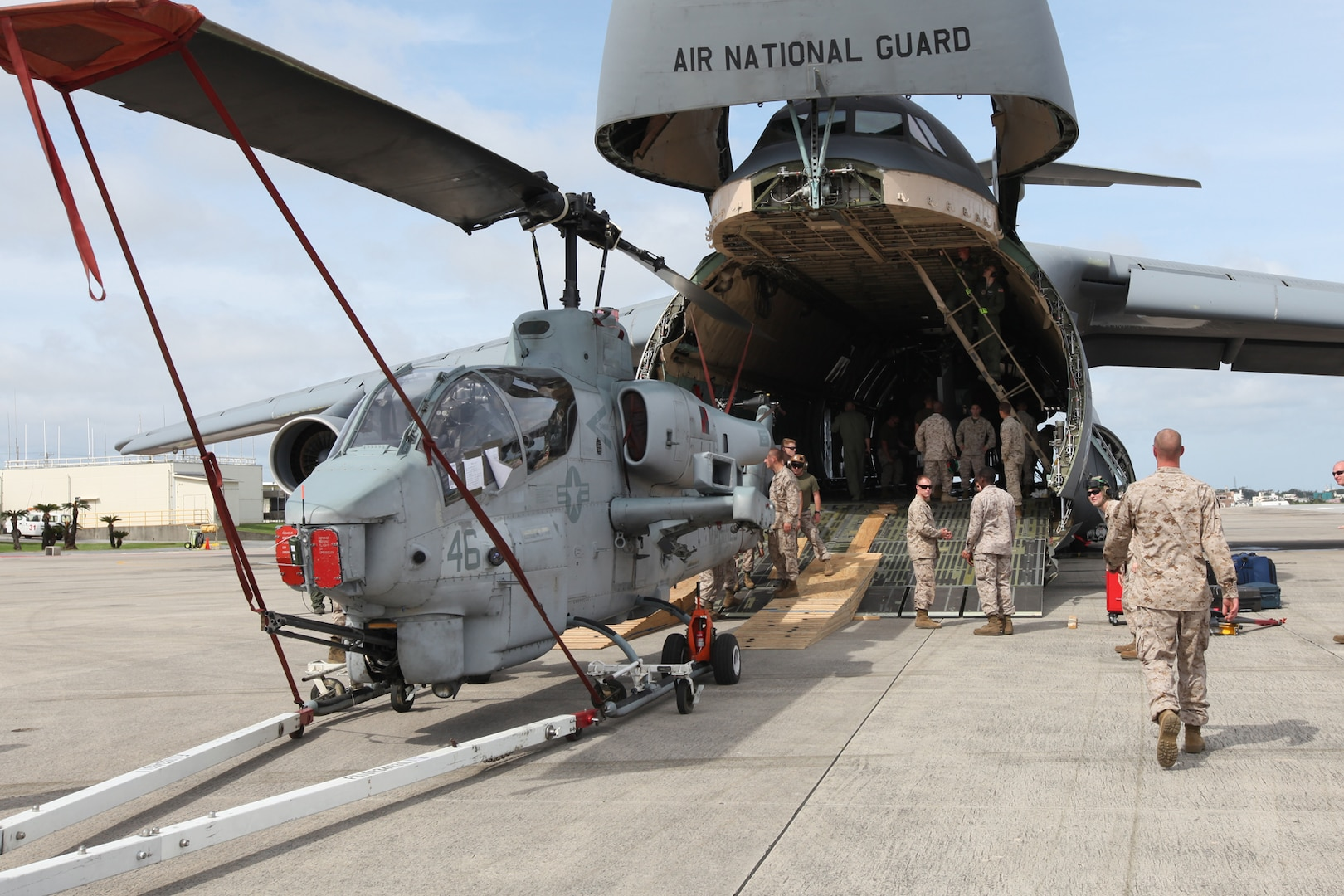 Marines from Marine Heavy Helicopter Squadron 772 (HMH-772) off load an AH-1U Cobra from a C-5 Galaxy on Marine Corps Air Station Futenma, Okinawa, Japan, June 7, 2013. The C-5 was carrying aircraft and personnel from HMH-772. HMH-772 is participating in the Unit Deployment Program. (U.S. Marine Corps photo by Lance Cpl. Jeraco Jenkins/ Cleared For Public Release).