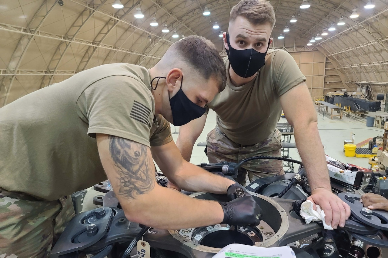 Two men work on a helicopter inside a hangar.