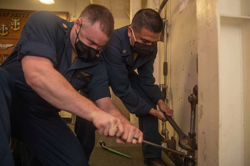 Two men in uniforms use wrenches to turn a pipe.