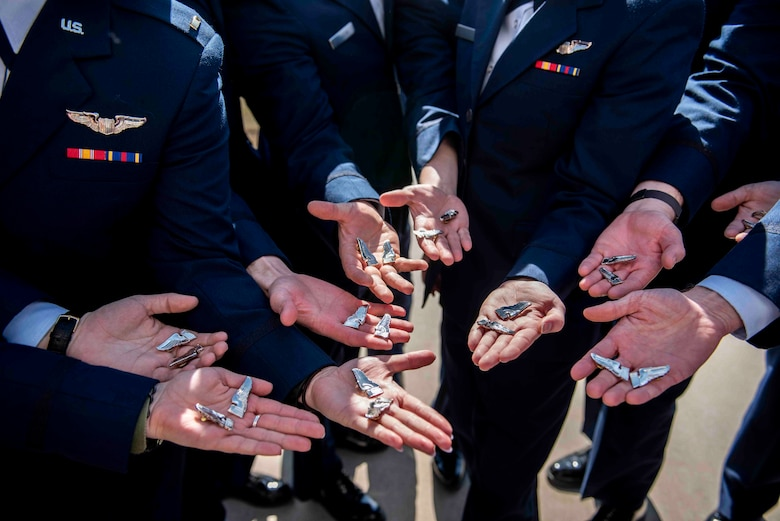 """Class 21-06AU graduated April 2 at Vance Air Force Base and soon after, demonstrated a tradition called """"breaking of the wings."""" After breaking the wings, one half stays with the pilot while the other is given to a loved one for safekeeping."""