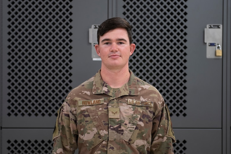 A photo of an Airman standing in front of lockers.