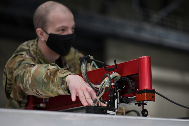 Airman First Class Seth Hardy, 319th Aircraft Maintenance Squadron nondestructive inspection journeyman, scans the wing of an RQ-4 Global Hawk with a mobile automated scanner system on Grand Forks Air Force Base, N.D., March 25, 2021. The MAUS inspection sends sound waves through the wing composite to identify potential defects on the interior of the aircraft. (U.S. Air Force photo by Airman 1st Class Ashley Richards)