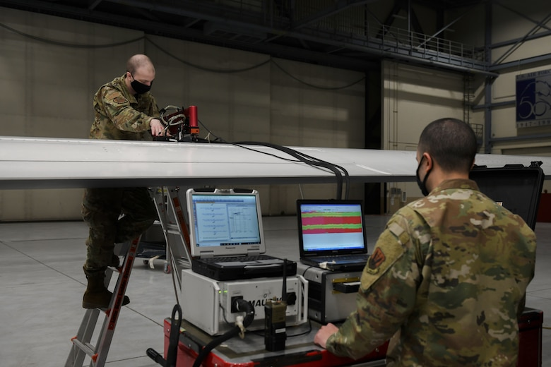 Airman First Class Seth Hardy, left/right, 319th Aircraft Maintenance Squadron nondestructive inspection journeyman, works alongside Senior Airman Harry Fraticelli, 319 AMXS NDI craftsman, to perform a scan using sound waves on the wing of an RQ-4 Global Hawk at Grand Forks Air Force Base, N.D., March 25, 2021. The scan is performed using a mobile automated scanner system as routine maintenance on the Global Hawk after every 150 flights. (U.S. Air Force photo by Airman 1st Class Ashley Richards)