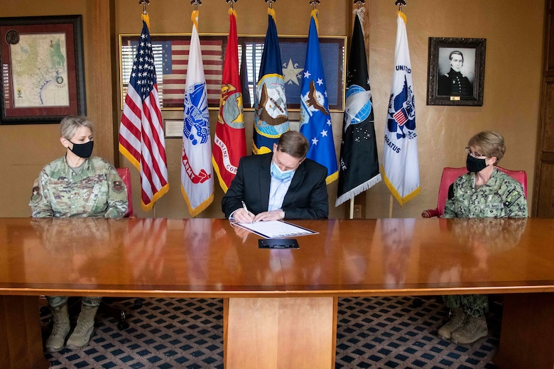 Robert Naething, U.S. Army North (Fifth Army) deputy to the commanding general, signs a proclamation honoring April as the Month of the Military Child on Joint Base San Antonio, while Brig. Gen. Caroline M. Miller, 502d Air Base Wing and JBSA commander, left, and Rear Adm. Cynthia Kuehner, Naval Medical Forces Support Command commander, right, look on.