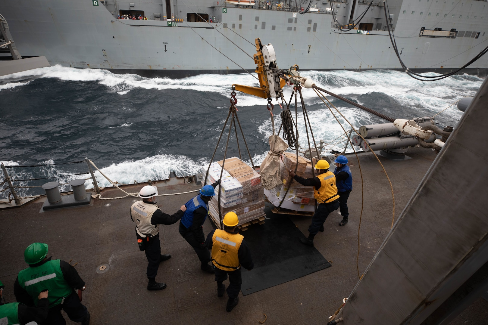 Sailors aboard the Arleigh Burke-class guided-missile destroyer USS Roosevelt (DDG 80) receive pallets of food stores during a replenishment-at-sea with the dry cargo ship USNS William McClean (T-AKE 12), April 1, 2021.
