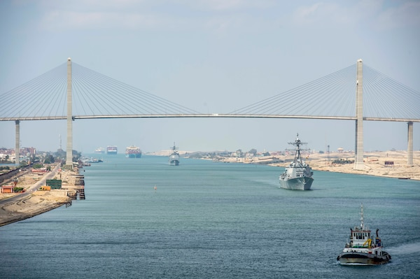 210402-N-EE423-1005 SUEZ CANAL (April 2, 2021) The guided-missile cruiser USS Monterey (CG 61), left, and the guided-missile destroyer USS Thomas Hudner (DDG 116) sail behind the aircraft carrier USS Dwight D. Eisenhower (CVN 69) during a Suez Canal transit, April 2. The Eisenhower Carrier Strike Group is deployed to the U.S. 5th Fleet area of operations in support of naval operations to ensure maritime stability and security in the Central Region, connecting the Mediterranean and Pacific through the Western Indian Ocean and three strategic choke points. (U.S. Navy photo by Mass Communication Specialist 2nd Class Sophie A. Pinkham)