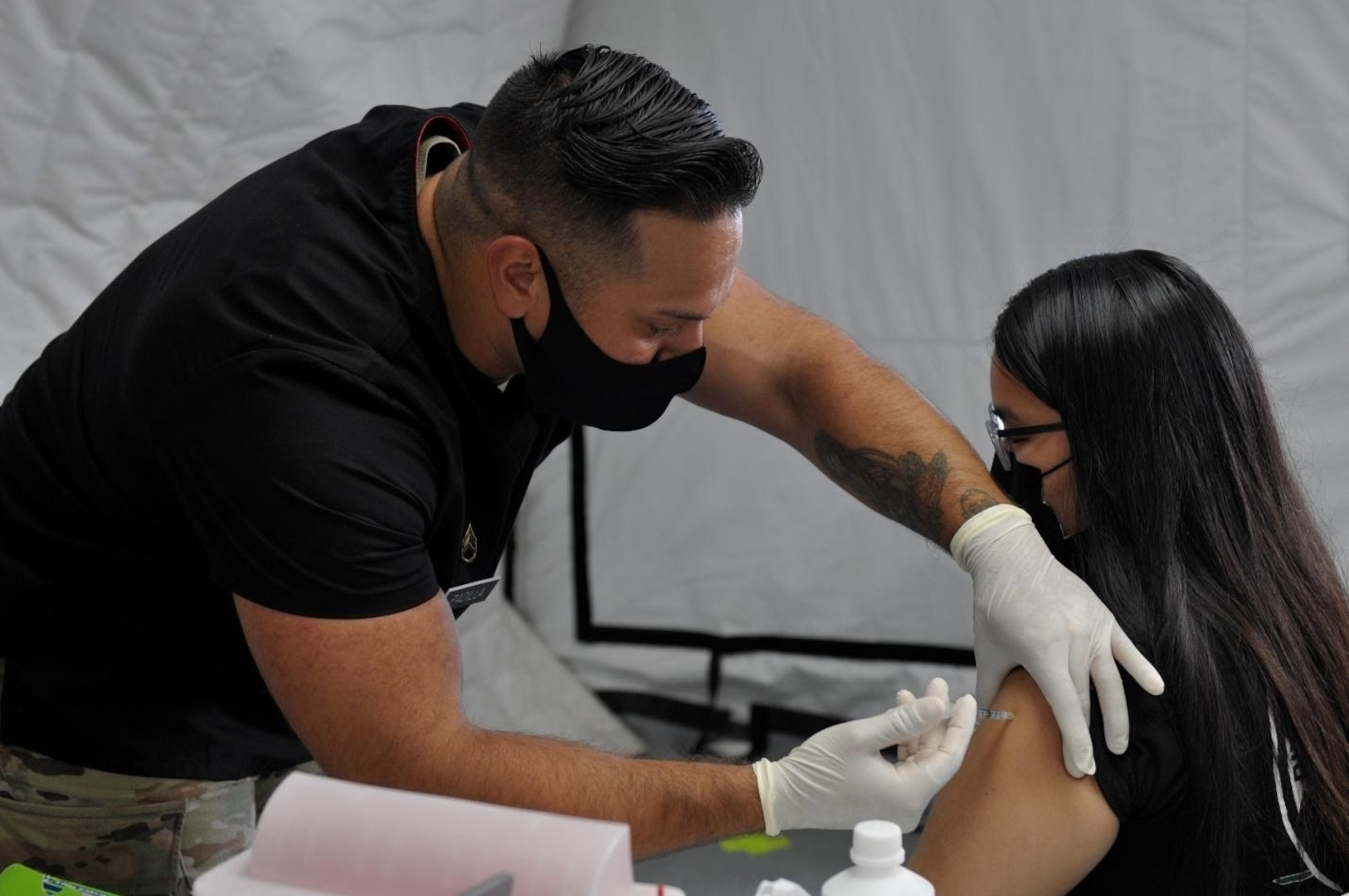 Staff Sgt. Joshua Padilla, assigned to 25th Infantry Division, administers a COVID-19 Vaccine in support of the Commonwealth Healthcare Corporation (CHCC) COVID-19 Vaccination team at the Medical Care and Treatment Site (MCATS).