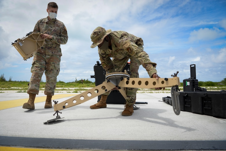 U.S. Air Force Master Sgt. Gilbert Kless, left, and Airman 1st Class Justin Brown, center, assigned to the 644th Combat Communications Squadron, set up a communication fly away kit during a field training exercise on Wake Island, Western Pacific, April 2, 2021.