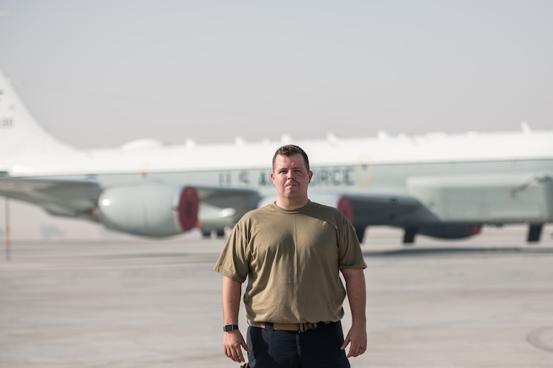 a man poses for a portrait in front of an airplane
